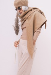 Stylish Details of everyday look. Model wearing casual beige outfit. Beret, scarf and fashion sunglasses. Trendy minimalistic style.