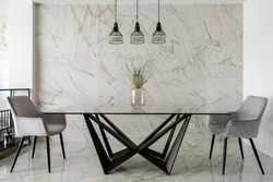 Stylish dining room with marble tiles on wall and floor and big, modern glass table with two chairs