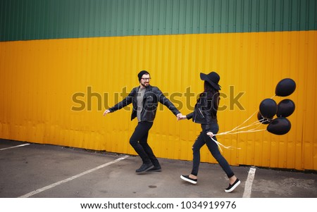 Stylish enamored guy and girl in leather jackets near a yellow green wall with black air balloons in hands #1034919976