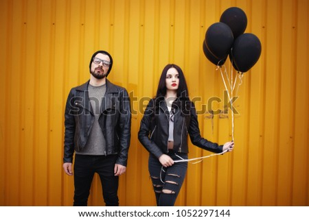 Stylish enamored guy and girl in leather jackets near a yellow green wall with black air balloons in hands #1052297144