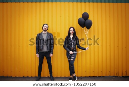 Stylish enamored guy and girl in leather jackets near a yellow green wall with black air balloons in hands #1052297150