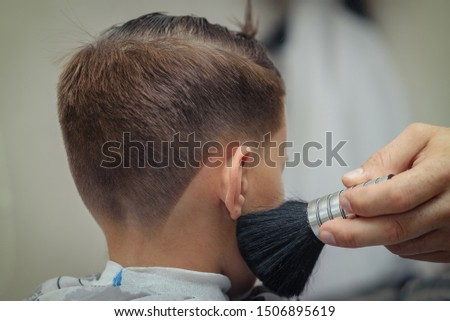 Stylish European boy getting hairstyling in barbershop.