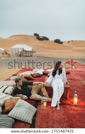 Stylish european couple in love enjoying evening together in luxury glamping camp in Sahara desert, Morocco. Romantic mood, lying on multicolor pillows.