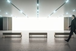 Stylish exhibition room with big white blank screen, gold color benches on concrete floor, glowing led lights and walking businessman. Mockup