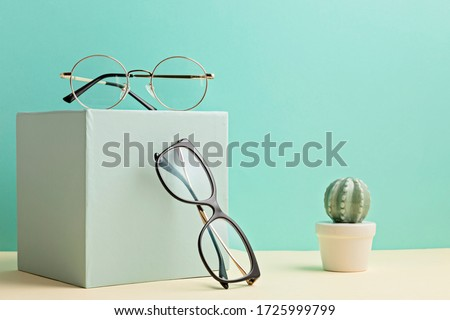 Photo of  Stylish eyeglasses over pastel  background. Optical store, glasses selection, eye test, vision examination at optician, fashion accessories concept. Front view