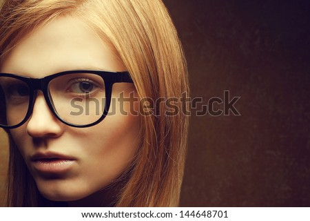 Stylish eyewear concept. Portrait of a young beautiful red-haired model (student) wearing trendy glasses and posing over golden background. Close up. Copy-space. Studio shot