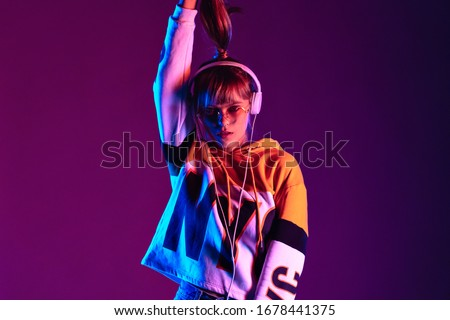 Stylish fashion igen teen hipster pretty girl model wear glasses headphones enjoy listen new trendy dance music mix look at camera hold ponytail stand at purple studio background 80s party, portrait
