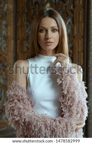 Stylish fashion tall female woman girl glamour model long brown hair pink coat white shirt poses camera stay hand up naked shoulders background vintage wooden aged interior
