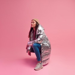 Stylish fashionable and modern young woman in a puffy light down jacket. The jacket is a silver metallic color. woman in street clothes, jeans and sneakers. Sits on a pink background