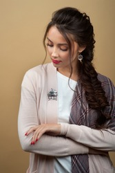 Stylish fashionable girl wears authentic accessories: silver brooch and earrings