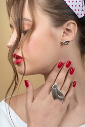 Stylish fashionable girl wears authentic accessories: silver ring and bird-shaped earrings, women's fashion, beauty, advertising concept. Close up studio portrait.