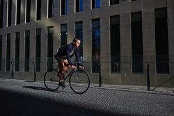 Stylish fashionable man riding on fixed gear bicycle in city