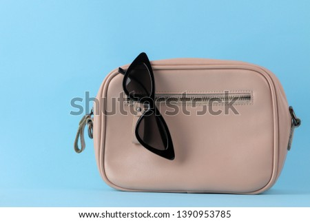 Stylish fashionable pink bag and women's accessories on a bright trendy naked background. female accessory concept.
