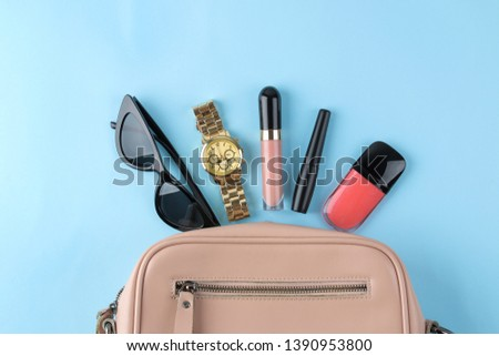 Stylish fashionable pink bag and women's cosmetics and accessories on a bright trendy naked background. female accessory concept. top view