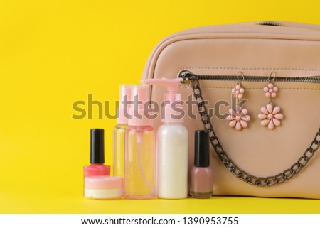 Stylish fashionable pink bag and women's cosmetics and accessories on a bright trendy yellow background. female accessory concept.