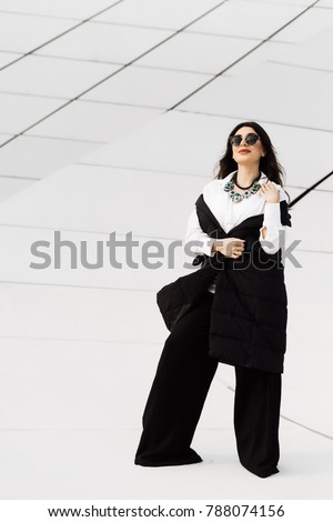 stylish fashionable woman in black suit and sunglasses posing in Baku