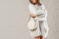 Stylish fashionable woman with trendy leather round white handbag bag. Model wearing white monochromatic outfit. Studio shot. Copy, empty space for text