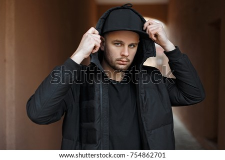 36167c9f9a9 Stylish fashionable young man in a trendy black baseball cap in a winter  fashion jacket with