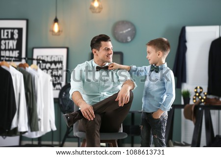 Stylish father and son in shirts, indoors