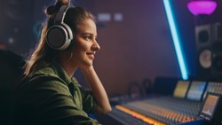 Stylish Female Audio Engineer / Producer Working in Music Record Studio, Uses Headphones, Mixer Board, Control Desk to Create New Song. Creative Artist Musician