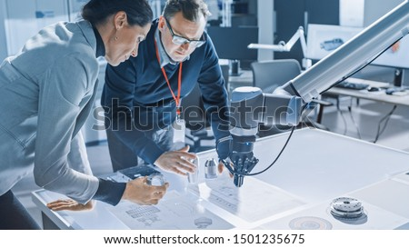 Stylish Female Engineer and Male Specialist Talking Lean on the Table Work with Blueprints, Documents and Tablet Computer. Working on Program and Manipulation of Robot Arm Movements. Modern Facility