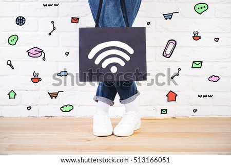 Stylish female in jeans and sneakers holding shopping bag with wi-fi signal icon. Various communication symbols around on white brick wall background