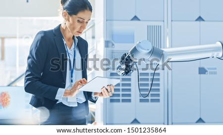 Stylish Female Industrial Robotics Engineer Uses Tablet Computer to Program and Manipulate Robot Arm for Lifting, Moving Objects. Technology Research Facility for Machine Learning and Cloud Computing