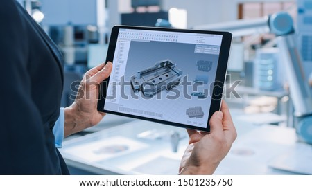 Stylish Female Industrial Robotics Engineer Uses Tablet Computer with CAD Software and to Manipulate and Program Robot Arm for Lifting Moving Objects. Technology Research Facility for Machine Learning