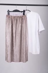 Stylish female oversize t-shirt and biege pleated skirt hanging on a rack. Fashion blog, website, social media hero header. Spring outfit. High quality photo