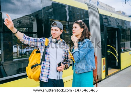 Stylish female traveler with backpack and smartphone in hand asking for help man with backpack at tram stop. Young woman tourist asking for directions and help from local people in tram stop outdoor.