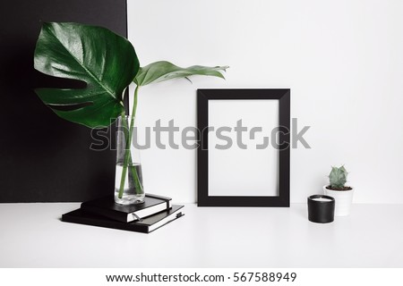 Stylish feminine space with monstera leaves in vase, cactus, notebooks, candle at home or studio with white and black background on shelf. Isolated mockup frame. Styled minimalistic still life