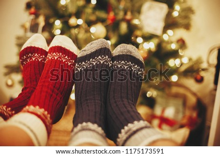 stylish festive socks on couple legs on background of golden beautiful christmas tree with lights in festive room. family relax time. cozy winter holidays. warm atmospheric moment