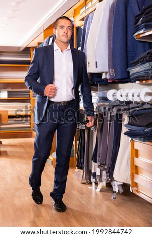 Stylish fine man visiting men clothes store in search of new look.