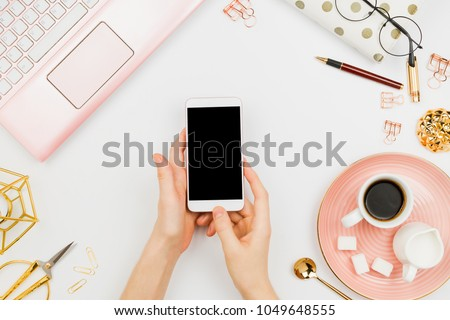 Stylish flatlay frame arrangement with woman's hands holding white smartphone with black copyspace, pink laptop, coffee, planner and other accessories. Feminine business mockup