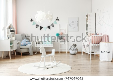 Stylish furniture in a monochromatic spacious kid's room with tulle pompons as decoration #747049042