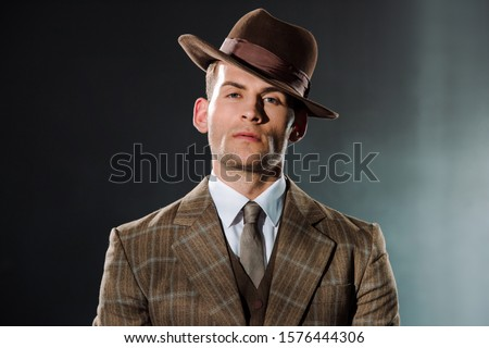 Photo of  stylish gangster in hat looking at camera on black