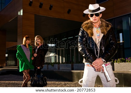Stylish gangster with a gun and two young women on background outdoors