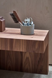 Stylish geometrical textured wooden stand with a light holder with a brown brush, scissors, pencils and marker pens in the illuminated interior. Closeup vertical photo.