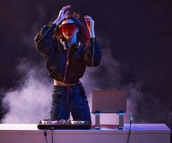 Stylish girl DJ in glasses headphones and a bomber mixes music dancing at a party in the neon light in the smoke .