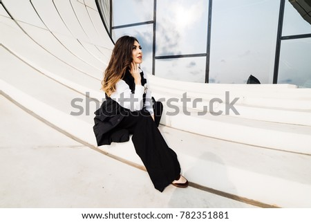 stylish girl in a black suit posing against the background of an unusual building in the city of Baku