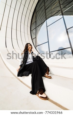 stylish girl in a black suit posing near an unusual building
