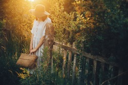 Stylish girl in linen dress holding rustic straw basket at wooden fence  in sunset light. Boho woman relaxing and posing in summer countryside in warm evening. Atmospheric rural moment