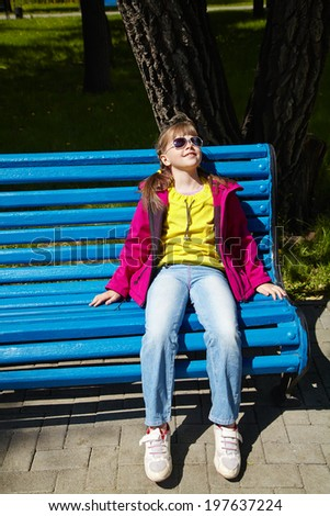 stylish girl in sunglasses sitting sitting on a park bench. children outdoors. vacation in the summer park