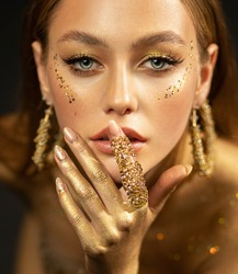 Stylish girl looks at camera. Gold ring on finger, earrings rings. Beautiful face, blue eyes, blonde hair, golden glamorous makeup, gold paint on body, skin, hands. Portrait of fashion model woman