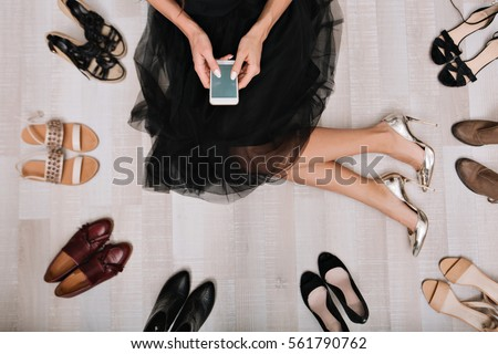 Shutterstock Stylish girl sitting on the floor in a dressing room with smartphone in hands, writes  the message, surrounded by a variety of shoes. She is dressed in a black skirt, on her feet silver luxury shoes