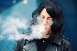 stylish girl smoking an e-cigarette as she is walking through the city. young woman smoking electronic cigarette