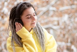 Stylish girl with dreadlocks in headphones closed her eyes happy listening to music outside. Trees in the snow on the background. Young woman in a yellow hoodie. Winter lifestyle concept. Copy space.