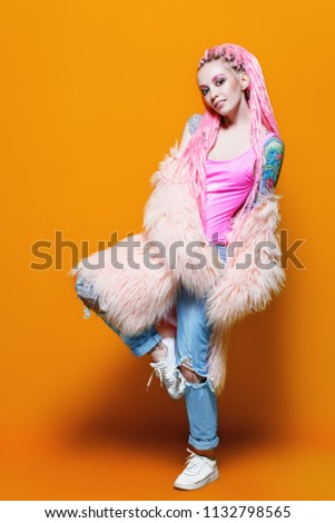 Stylish girl with pink dreadlocks posing in bright clothes on a yellow background. Full length portrait. Beauty, fashion. #1132798565