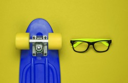 Stylish glasses without lenses, cruiser board on yellow background. Hipster gear. Top view