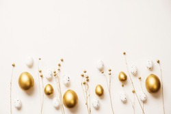 Stylish golden eggs easter concept. Easter gold eggs with golden dried flax linum bunch white background. Flat lay trendy easter. Happy easter card. Copy space for text